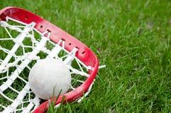 De lacrosse hoofd en grijze bal van meisjes op gras stock foto