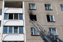 De ladder van brandmotor aan een brandend huis stock afbeeldingen