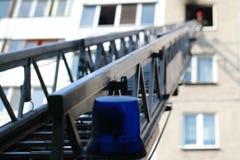 De ladder van brandmotor aan een brandend huis stock fotografie