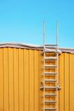 De ladder van het metaal op gele muur stock fotografie