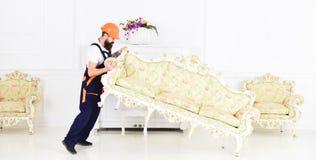 De lader beweegt bank, laag De koerier levert meubilair uit in het geval van beweging, verhuizing Het concept van de leveringsdie royalty-vrije stock foto