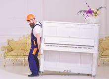 De lader beweegt pianoinstrument De koerier levert meubilair, beweging uit, verhuizing Mens met baardarbeider in helm en royalty-vrije stock foto's