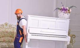 De lader beweegt pianoinstrument De mens met baard, arbeider in overall en helm heft piano, witte achtergrond op koerier stock fotografie