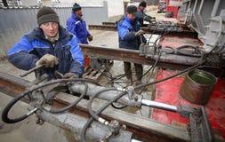 De lader beweegt zware lading op sporen gebruikend hydraulische opdringers Royalty-vrije Stock Afbeelding