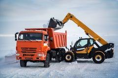 De lader laadt de sneeuw in de kipwagen royalty-vrije stock afbeeldingen