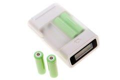 De lader van de batterij met vier batterijen van aa. Stock Afbeeldingen
