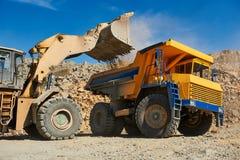 De ladingserts van de wiellader in stortplaatsvrachtwagen bij bovengronds royalty-vrije stock foto