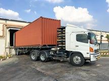 De ladingsgoederen van de containervrachtwagen bij pakhuis Stock Afbeelding