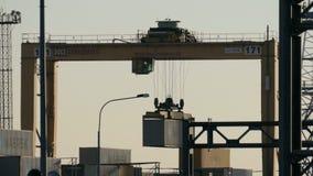De ladingskraan met cabine heft de container op stock videobeelden