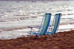 De lado a lado sillas de playa Fotos de archivo libres de regalías