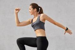 De lado tirado de mujer activa el estar en el movimiento, tiene cola de potro, lleva sportsclothes, presenta contra fondo gris, s fotos de archivo