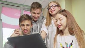 De lage hoek bebouwde schot van groep die tienerjaren, gebruikend laptop samen bestuderen stock video