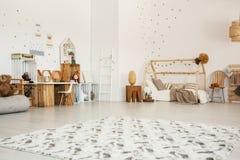 De lage hoek van een binnenland van de meisjes` s slaapkamer met een gevormde deken, streeft na Stock Foto