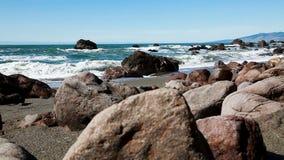 De lage Rotsen van de Camerahoek op Strand met Oceaangolven stock videobeelden