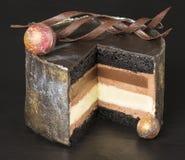 De lagen van de chocoladecake met krullen, close-up op een donkere achtergrond worden verfraaid die Selectieve nadruk Stock Foto's