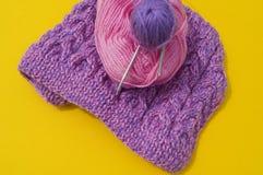 De lagen van wolroze en purple liggen naast een afgekoppeld GLB Gele achtergrond stock foto's