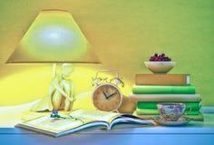 De lamp, boeken, uren, kop thee, plaat wordt van kers gevestigd op een lijst Stock Afbeeldingen