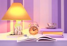 De lamp, boeken, uren, kop thee wordt gevestigd op een lijst aangaande een lilac achtergrond Royalty-vrije Stock Fotografie