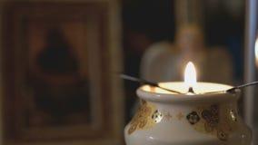 De lamp van de kerkolie met een brandende kaars in kerk stock video