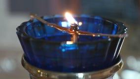 De lamp van de kerkolie met een brandende kaars in tempel stock video