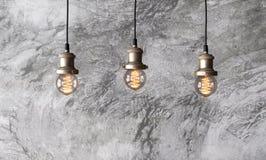 De lampen van de zoldertegenhanger op de achtergrond van ruw cementpleister Royalty-vrije Stock Afbeelding