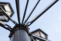 De lamppost wordt gemaakt van metaal tegen een blauwe hemel met uithangborden van steden stock foto