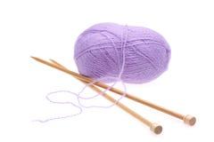 De lana violeta una cuerda de rosca con los rayos para hacer punto Fotografía de archivo