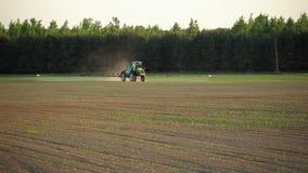 De landbouwbedrijftractor bevrucht het gebied van de neveltarwe met spuitbus van pesticideherbicide stock videobeelden