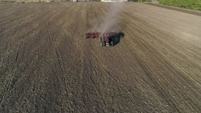 De landbouwbedrijftractor met ploeg cultiveert agrarisch land op gebied alvorens landbouwgewassen te zaaien stock videobeelden