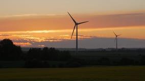 De landbouwbedrijven van windturbines met stralen van licht bij zonsondergang stock afbeelding