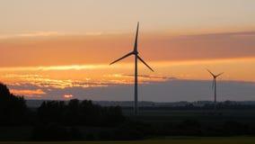 De landbouwbedrijven van windturbines met stralen van licht bij zonsondergang royalty-vrije stock fotografie