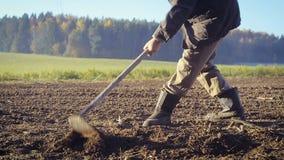 De landbouwer behandelt het land met een schoffel stock videobeelden