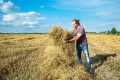 De landbouwer controleert de kwaliteit van het stro royalty-vrije stock afbeelding