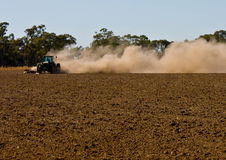 De landbouwer heft wolken van stof op aangezien hij zijn droog ploegt Royalty-vrije Stock Fotografie