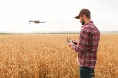 De landbouwer houdt ver controlemechanisme met zijn handen terwijl quadcopter op achtergrond vliegt De hommel hangt achter stock afbeelding