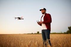 De landbouwer houdt ver controlemechanisme met zijn handen terwijl quadcopter op achtergrond vliegt De hommel hangt achter stock afbeeldingen