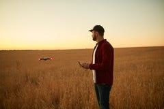 De landbouwer houdt ver controlemechanisme met zijn handen terwijl quadcopter op achtergrond vliegt De hommel hangt achter royalty-vrije stock afbeelding