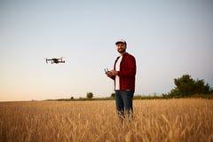 De landbouwer houdt ver controlemechanisme met zijn handen terwijl quadcopter op achtergrond vliegt De hommel hangt achter royalty-vrije stock afbeeldingen