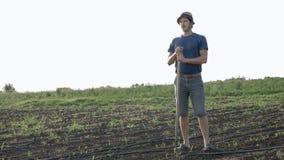 De landbouwer met schoffel rust terwijl onkruid op graangebied bij organisch landbouwbedrijf verwijdert Royalty-vrije Stock Afbeeldingen