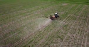 De landbouwer op een tractor met een spuitbus maakt meststof stock videobeelden