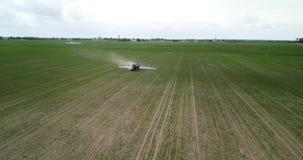 De landbouwer op een tractor met een spuitbus maakt meststof stock footage