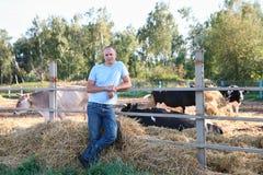 De landbouwer werkt aan landbouwbedrijf met melkkoeien Royalty-vrije Stock Afbeeldingen