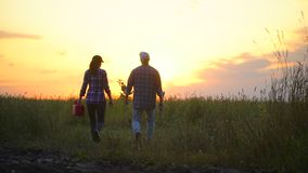 De landbouwersman en de vrouw, landbouwers koppelen het lopen op gebied bij zonsondergang of zonsopgang Draag boomzaailing, giete stock videobeelden