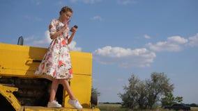 De landelijke die vrouw aan telefoon op kap wordt gefotografeerd van maaidorser op aard stock footage