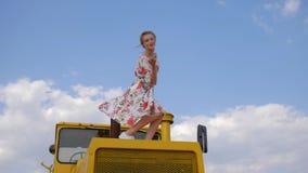 De landelijke jonge vrouw in kleding geeft luchtkus en golven zijn hand op blauwe hemelachtergrond met witte wolken stock video