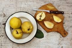 De landelijke vruchten van de stilleven rijpe gele kweepeer op de plaat en de besnoeiing Stock Foto's