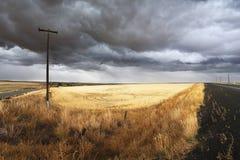De landelijke weg van de grond en kolommen van een elektrische leiding Stock Foto