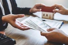 De landgoedagent huis geven en de sleutels die tot cliënt na het ondertekenen van overeenkomst gaan onroerende goederen met goedg royalty-vrije stock foto
