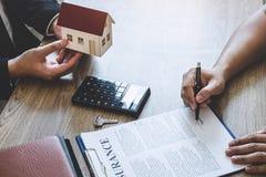 De landgoedagent huis geven en de sleutels die tot cliënt na het ondertekenen van overeenkomst gaan onroerende goederen met goedg royalty-vrije stock afbeeldingen