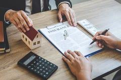 De landgoedagent huis geven en de sleutels die tot cliënt na het ondertekenen van overeenkomst gaan onroerende goederen met goedg royalty-vrije stock afbeelding